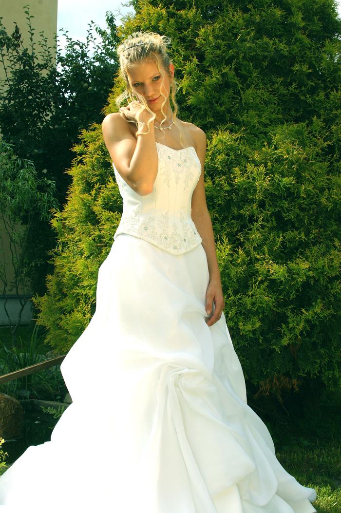 3d06cafe86c3 Kostkovaný korzet zdobený krajkovou mřížkou se šněrováním na zádech  doplňuje bohatě řasená sukně z bílého sametu