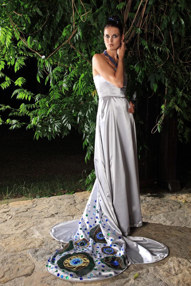 5182a781c266 Avantgardní svatební nebo náročné společenské šaty ze stříbřitěšedého  krepsaténu. Dlouhá členěná vlečka je zdobena našitými oky